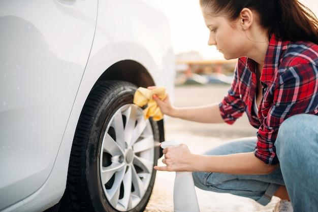 Mulher limpa o disco da roda do carro com spray