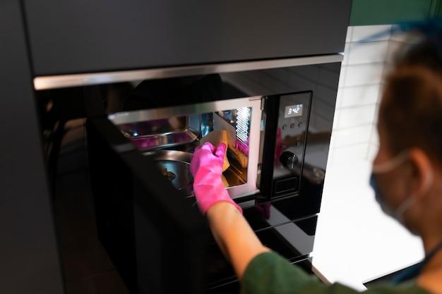 Mulher limpa o microondas