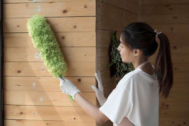 Mulher limpadora limpando com espanador