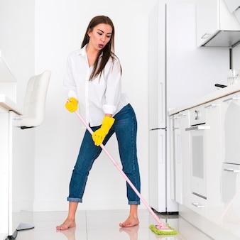 Mulher limpando a cozinha com uma esfregona