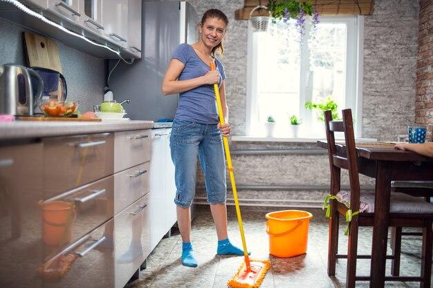 Mulher limpando a cozinha lava o chão em casa