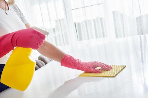 Mulher limpando a mesa da casa, higienizando a superfície da mesa da cozinha com frasco spray desinfetante