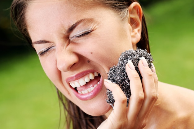 Mulher limpando a pele com escova metálica