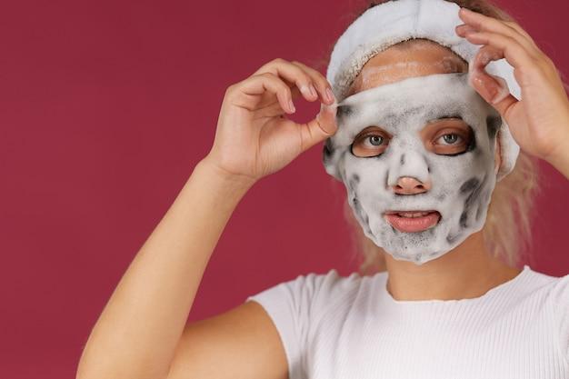 Mulher limpando a pele do rosto e se divertindo com espuma de limpeza de bolhas