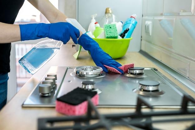 Mulher limpando a superfície do gás de aço inoxidável na cozinha com luvas de borracha.