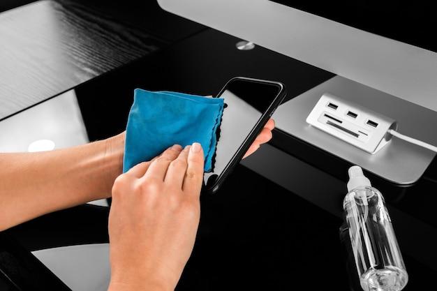 Mulher limpando a tela do celular com desinfetante na madeira. limpando a tela do smartphone para evitar o vírus corona covid 19