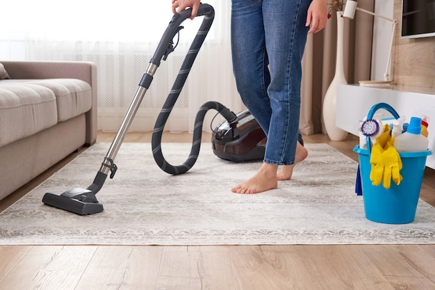 Mulher limpando carpete com aspirador de pó na moderna sala de estar