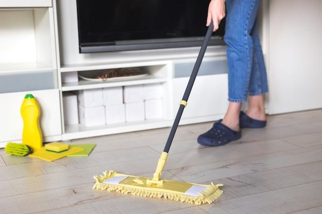 Mulher limpando chão com esfregão amarelo em casa