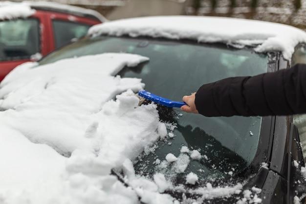 Mulher limpando neve do carro com escova