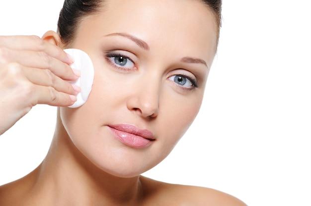 Mulher limpando o rosto com cotonete