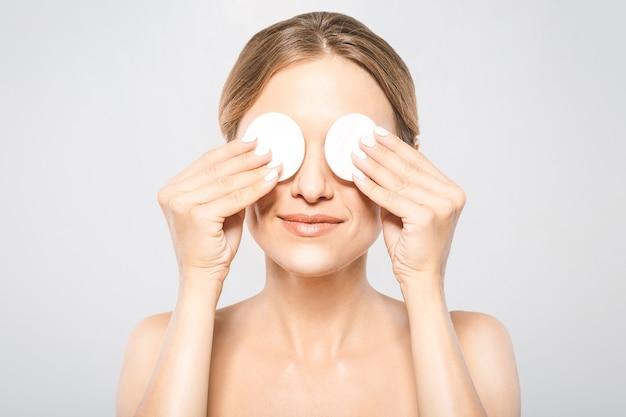Mulher limpando o rosto com uma almofada de algodão