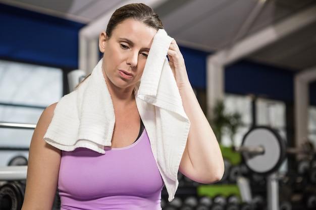 Mulher, limpando o suor com toalha no ginásio