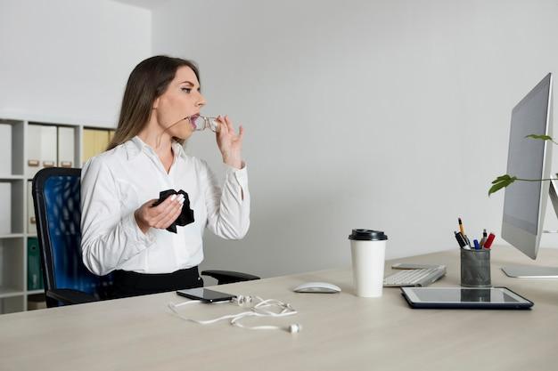 Mulher limpando os óculos no trabalho