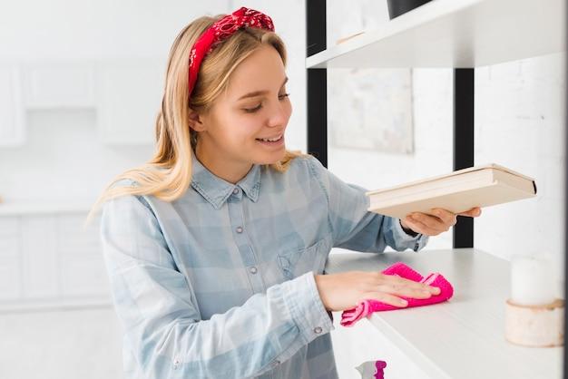 Mulher limpando prateleiras em casa