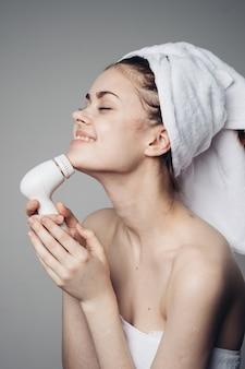 Mulher limpando rosto com escova de massagem