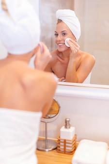Mulher limpando rosto em frente ao espelho