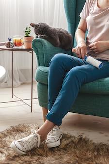 Mulher limpando roupas com rolo pegajoso de cabelo de gato.