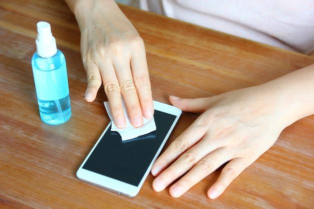 Mulher limpando seu telefone celular com desinfetante durante o dia útil de vista superior em surto de vírus