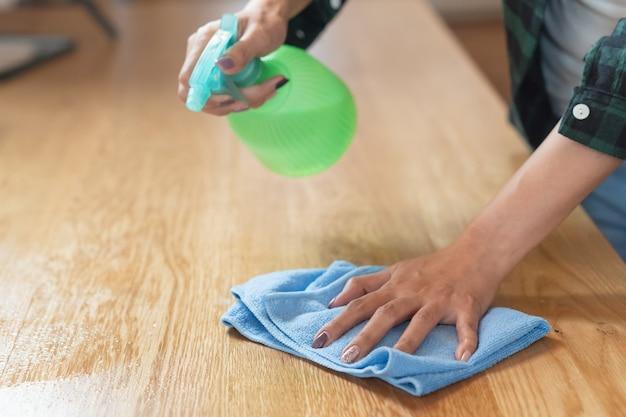 Mulher limpeza cozinha usando limpador spray e pano.