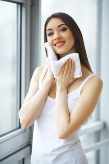 Mulher, limpeza de pele do rosto com toalha branca