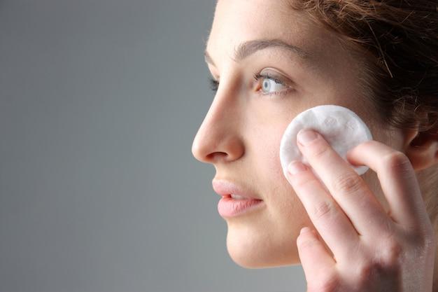 Mulher, limpeza, rosto, com, algodão, disco