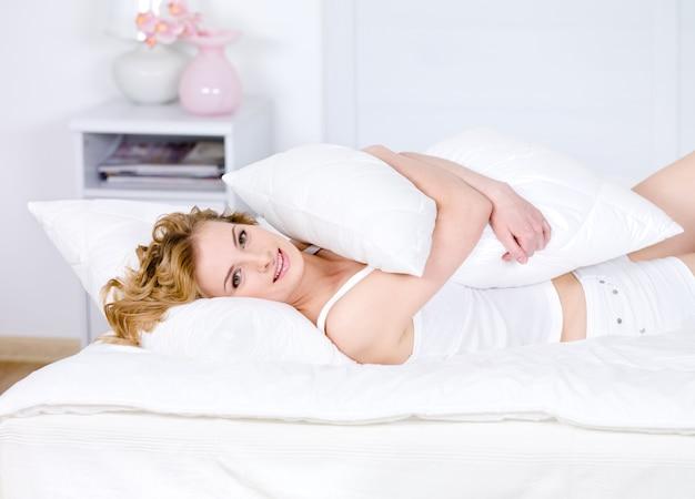 Mulher linda abraçando o travesseiro e relaxando em uma cama