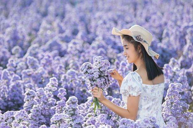 Mulher linda apreciando o campo de flores