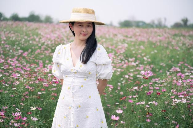 Mulher linda asiática com vestido branco no jardim de flores