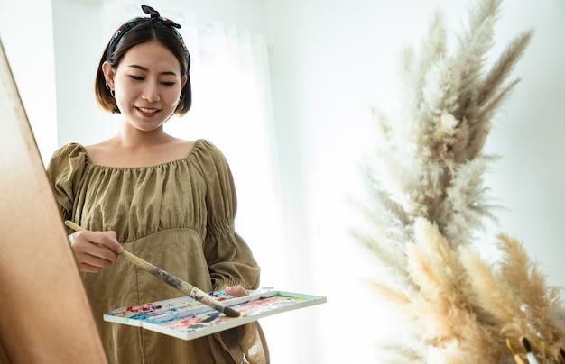 Mulher linda asiática em um campo de verão com pincel de desenho e tintas coloridas em pranchetas de papel no estúdio.