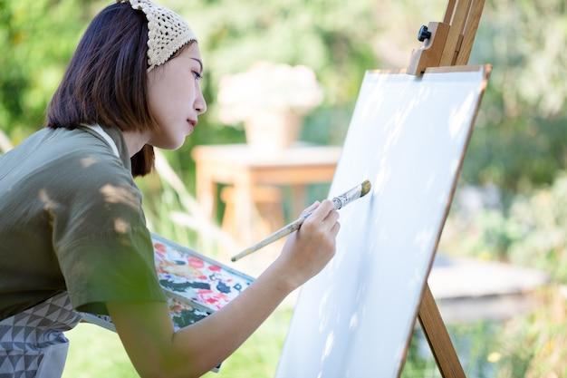 Mulher linda asiática em um campo de verão com pincel de desenho e tintas coloridas em pranchetas de papel no jardim.