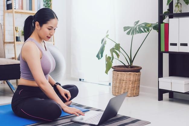Mulher linda asiática exercitar em casa e assistir o vídeo de treinamento no laptop.