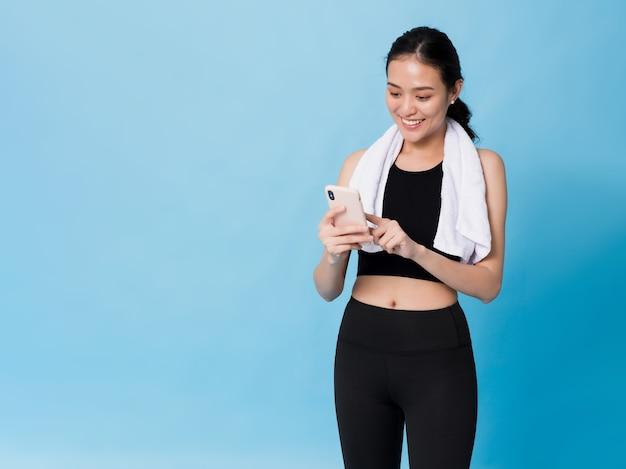 Mulher linda asiática feliz usando smartphone após exercício isolado em azul