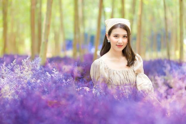 Mulher linda asiática que usa vestido está sentada no jardim de flores roxas e sorrindo feliz.