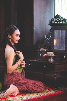 Mulher linda asiática, tailandesa ela está usando um vestido tailandês vintage e está penteando o cabelo na frente de um espelho no camarim.