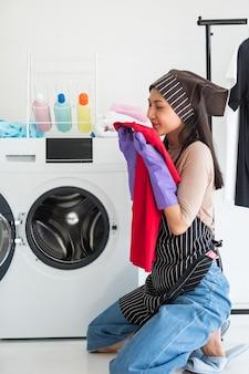 Mulher linda asiática verificar o cheiro de camiseta vermelha após a lavagem e secagem na máquina de lavar. trabalho doméstico para dona de casa ou empregada doméstica. higiene e conceito de estilo de vida saudável.