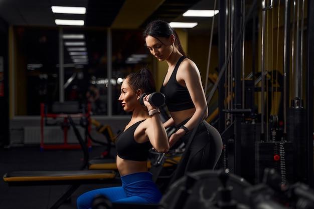 Mulher linda atleta se exercitando com halteres no clube de fitness