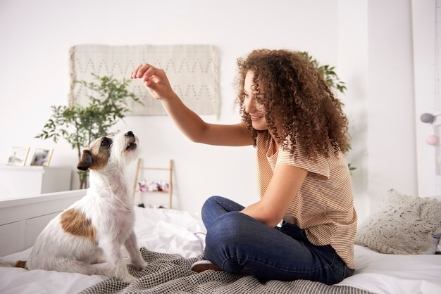Mulher linda brincando com cachorro na cama