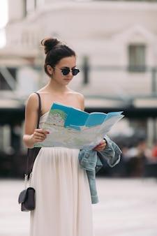Mulher linda caucasiana turista olhando para o mapa nas ruas da cidade