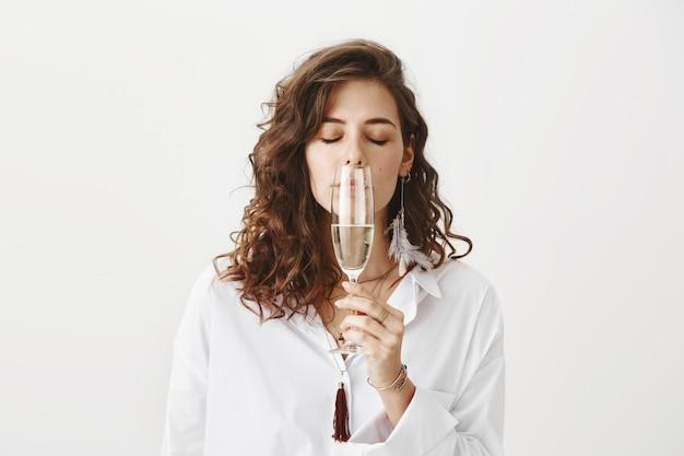 Mulher linda cheirando vinho
