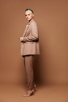 Mulher linda com cabelo loiro em um terno estiloso posando contra uma modelo feminina loira de fundo bege com maquiagem perfeita usando roupa oficial sobre fundo bege