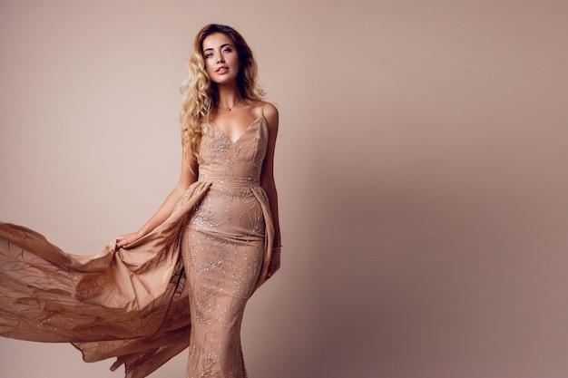 Mulher linda com cabelos loiros ondulados, usando elegante vestido bege