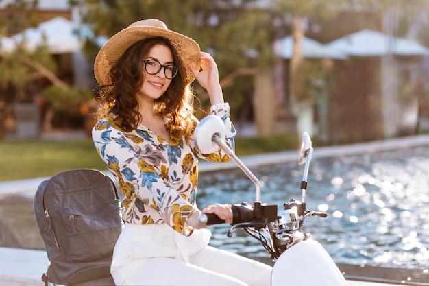 Mulher linda com cachos castanhos brilhantes olhando com interesse segurando seu chapéu de verão