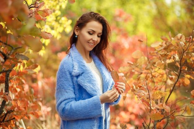 Mulher linda com casaco azul andando no parque outono e brincar com folhas amarelas.