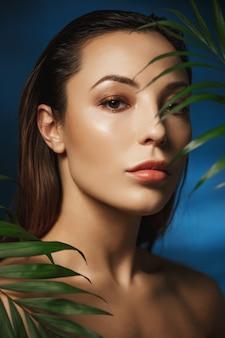 Mulher linda com maquiagem linda e fresca. atrás de folhas verdes.