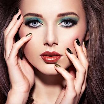 Mulher linda com maquiagem verde e unhas com cores criativas