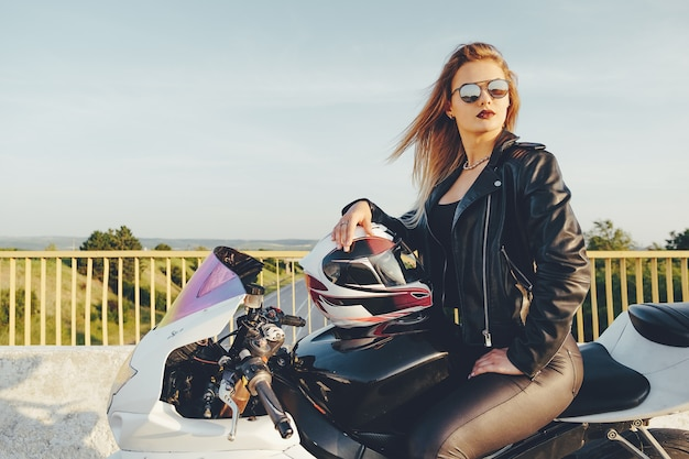 Mulher linda com óculos de sol dirigindo moto