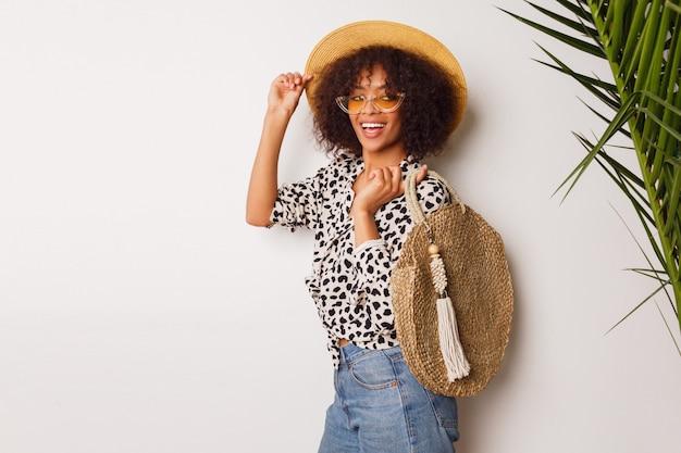 Mulher linda com pele escura em jeans e chapéu de palha posando no estúdio, sobre fundo branco, com saco no estilo de bali. sopping humor.