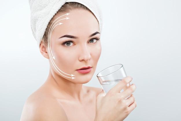 Mulher linda com sobrancelhas escuras e ombros nus, usando uma toalha branca na cabeça segurando um copo d'água