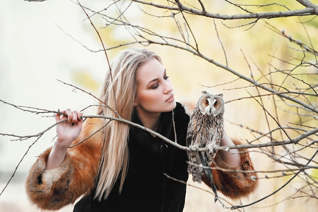 Mulher linda com um casaco de pele com uma coruja no braço. loira com cabelos longos na natureza, segurando uma coruja. imagem delicada romântica de uma menina
