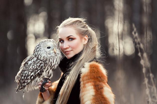 Mulher linda com um casaco de pele com uma coruja no braço. loira com cabelos longos na natureza